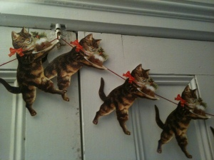 Cats bearing Christmas puddings. We found this in a cat-themed shop on a little street on the Left Bank in Paris a few years ago, and bought it partly because the cats look like our fat calico, Bayona. Now it's strung up on the French doors in the Manse's living room, and yes, those doors desperately need a scrubdown and a new coat of paint. Don' t think we don't know it!