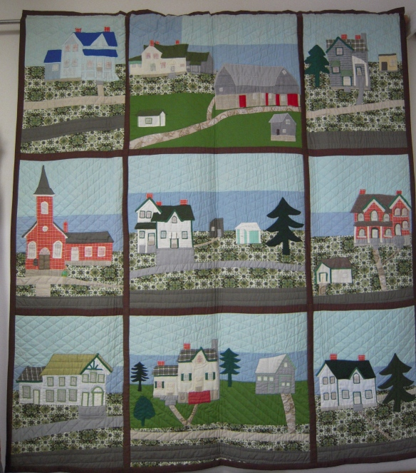 Goldie Holmes's most famous quilt, featuring Queensborough homes and buildings. Top row, left to right (warning: I am going to name the inhabitants as they were back in my day, which was also Goldie's day): Mrs. Barry's house, the Leslies' house and John Thompson's barn (both no longer standing), and the Wilson house. Middle row, from left: St. Andrew's United Church, Goldie and Art Holmes's home (complete with outhouse!) and the Manse. Bottom row, from left: the Orange Hall, Carl and Lois Gordon's house (where Chuck and Ruth Steele now live), and the Walkers' house (where Brian and Sylvia MacNeil now live).
