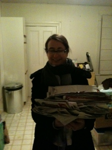 Me in the Manse kitchen one recent Friday night with an especially good haul: we'd been away for four weeks, so in the mailbox were four weeks' worth of the local newspapers. Gold!