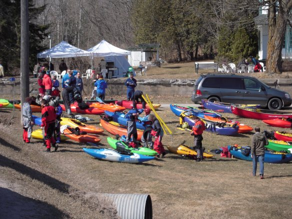 The kayaks made for a colourful spectacle once pulled up on land. Meanwhile, in the background you can see the tents where community volunteers were serving up barbecued burgers, homemade pie and hot coffee to the cold and hungry kayakers. (Photo by Raymond Brassard)