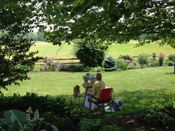 A painter in the garden of Kathy and David Rice on the Friends of the Tweed Library Garden Tour