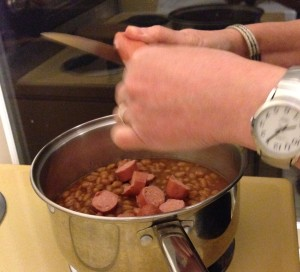 slicing the wieners into the beans