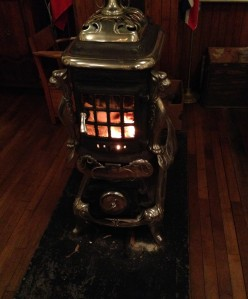 A cheery fire blazes in the wood stove at the front of the schoolroom.